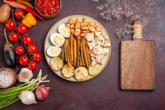 Bovenaanzicht gekookte groenten met eiermeel en verse groenten op donkere vloer maaltijd lunch plantaardige product