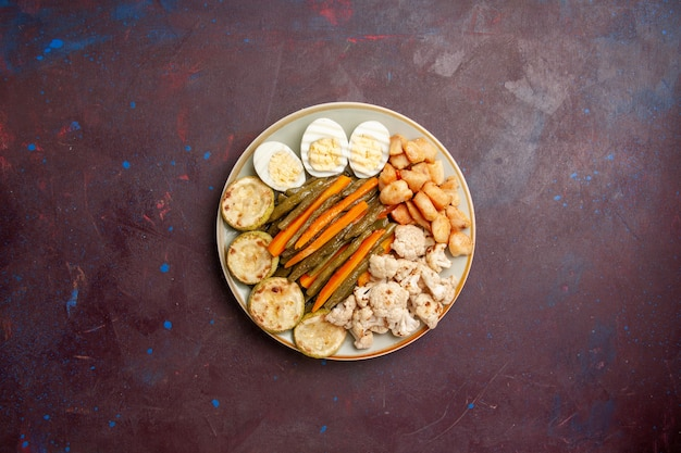 Bovenaanzicht gekookte groenten met eiermeel op een donkere ruimte