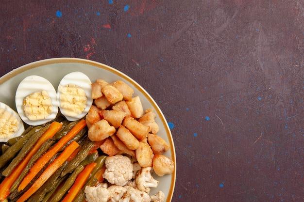 Bovenaanzicht gekookte groenten met eimeel op donkere ruimte