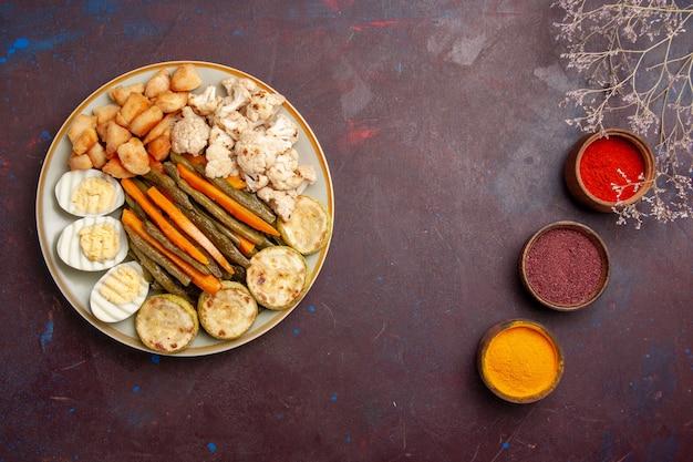 Bovenaanzicht gekookte groenten met verschillende kruiden op donkere ruimte