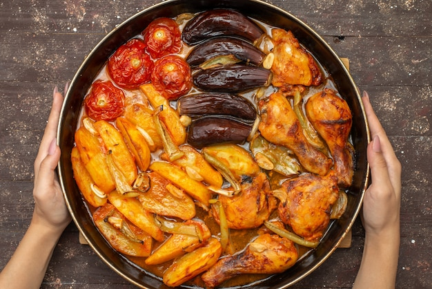 Bovenaanzicht gekookte groenten zoals aardappelen, tomaten en aubergines in de pan op bruin