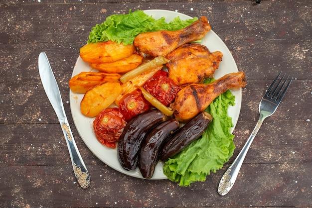 Bovenaanzicht gekookte groenten zoals aardappelen tomaten en aubergines met vlees in witte plaat met salade op bruin