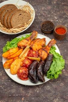 Bovenaanzicht gekookte groenten zoals aardappelen, tomaten en aubergines met vlees in witte plaat met salade op bruine, plantaardige maaltijd diner eten