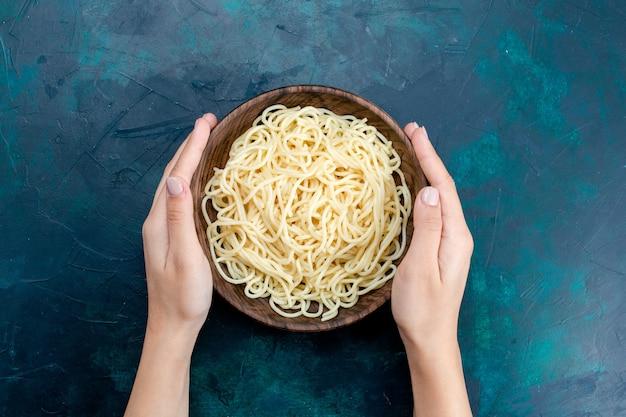 Bovenaanzicht gekookte italiaanse pasta binnen ronde houten plaat op de blauwe achtergrond pasta italië eten diner deeg vlees