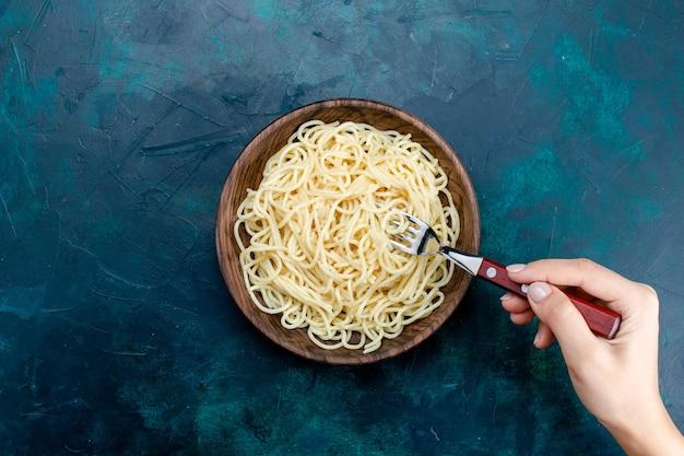 Bovenaanzicht gekookte italiaanse pasta binnen ronde houten plaat op de donkerblauwe achtergrond pasta italië eten diner deeg vlees