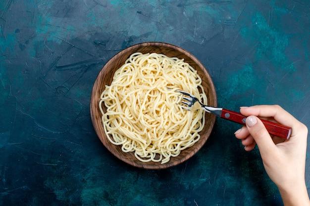 Bovenaanzicht gekookte italiaanse pasta binnen ronde houten plaat op het blauwe bureau pasta italië eten diner deeg vlees