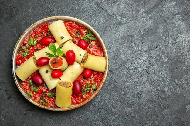 Bovenaanzicht gekookte italiaanse pasta heerlijke maaltijd met vlees en tomatensaus op de grijze achtergrond pasta deeg vlees saus eten