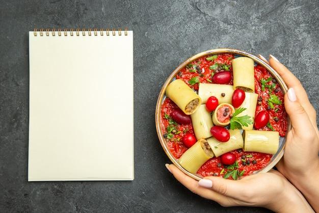 Bovenaanzicht gekookte italiaanse pasta heerlijke maaltijd met vlees en tomatensaus op donkere grijze achtergrond pasta deeg vlees saus eten