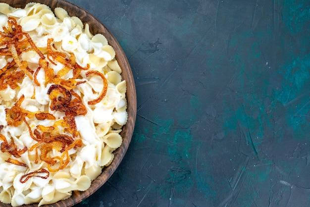 Bovenaanzicht gekookte italiaanse pasta met gebakken uien op blauw