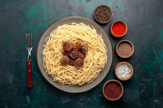 Bovenaanzicht gekookte italiaanse pasta met gehaktballen en kruiden op het donkerblauwe oppervlak