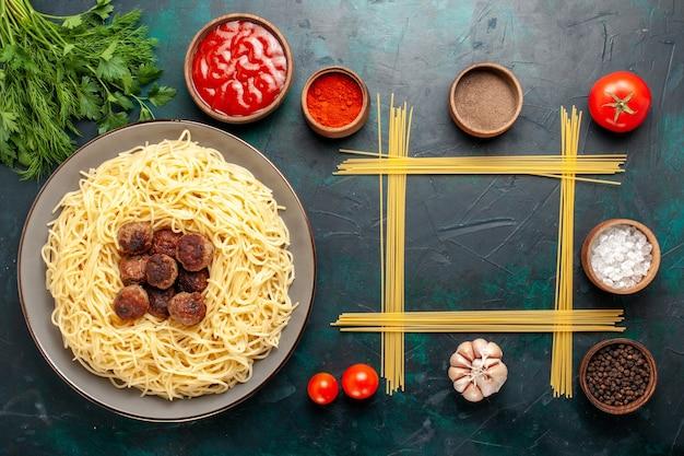 Bovenaanzicht gekookte italiaanse pasta met gehaktballen en verschillende kruiden op het blauwe oppervlak
