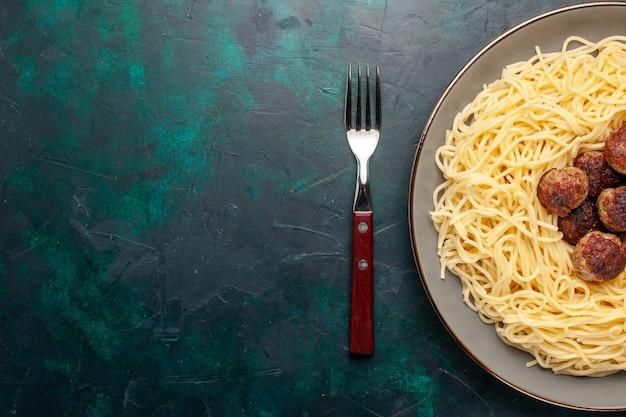 Bovenaanzicht gekookte italiaanse pasta met gehaktballen op het donkerblauwe bureau