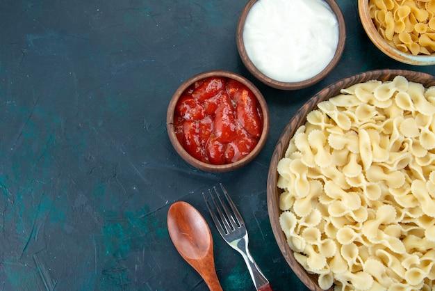 Bovenaanzicht gekookte italiaanse pasta met kruiden op donker