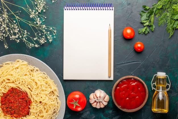 Bovenaanzicht gekookte italiaanse pasta met tomatensaus gehakt en olie op blauwe ondergrond