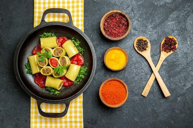 Bovenaanzicht gekookte italiaanse pasta met vlees en verschillende kruiden op grijze ruimte