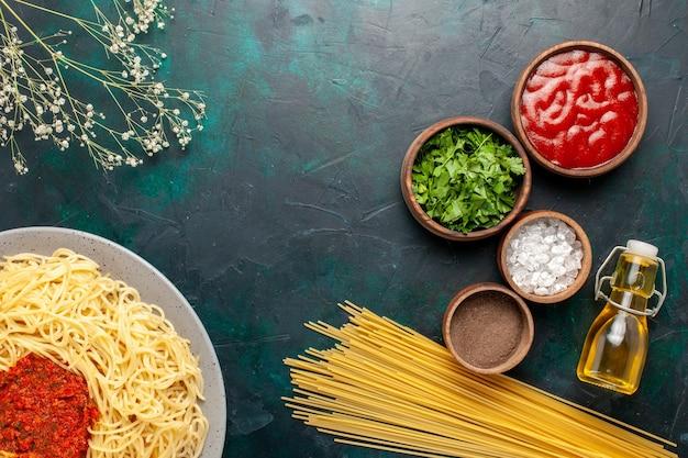 Bovenaanzicht gekookte italiaanse pasta met vlees en verschillende kruiden op het donkerblauwe oppervlak
