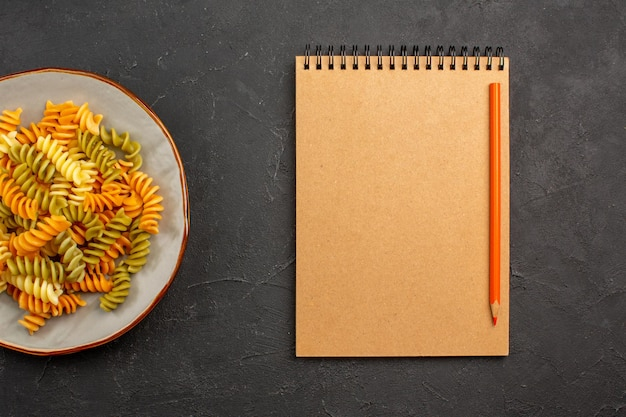 Bovenaanzicht gekookte italiaanse pasta ongebruikelijke spiraal pasta binnen plaat op de donkere ruimte