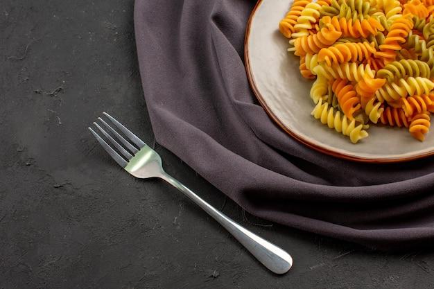 Bovenaanzicht gekookte italiaanse pasta ongebruikelijke spiraal pasta binnen plaat op donkere bureau pasta maaltijd diner eten kookschotel