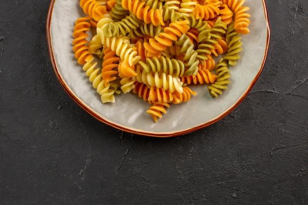 Bovenaanzicht gekookte italiaanse pasta ongebruikelijke spiraal pasta binnen plaat op donkere vloer maaltijd koken pasta gerecht diner