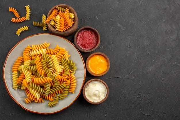 Bovenaanzicht gekookte italiaanse pasta ongebruikelijke spiraalpasta met kruiden op de donkere ruimte