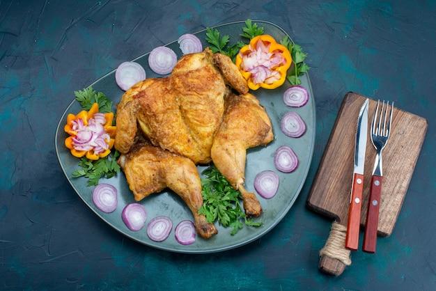 Bovenaanzicht gekookte kip met greens in plaat op het donkerblauwe bureau kippenvlees eten diner vlees