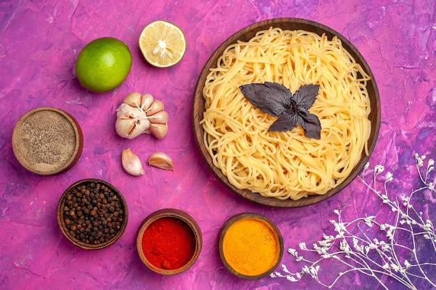 Bovenaanzicht gekookte lekkere spaghetti met kruiden op roze tafelmaaltijd pastagerecht
