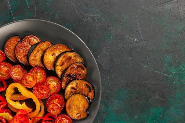 Bovenaanzicht gekookte paprika met aubergines op donkergroen oppervlak