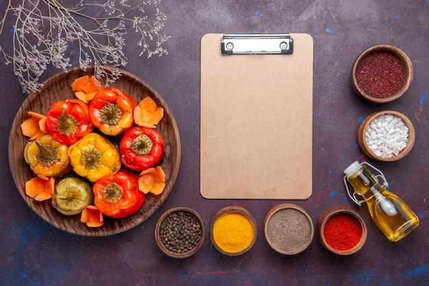 Bovenaanzicht gekookte paprika met gehakt en verschillende kruiden op donkere ondergrond vlees groenten rundvleesmeel