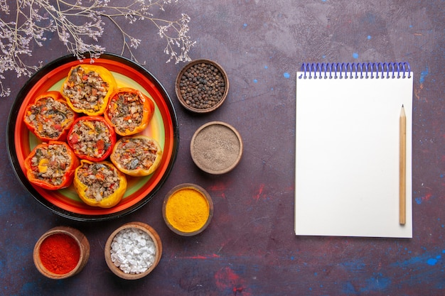 Bovenaanzicht gekookte paprika met gehakt en verschillende kruiden op een grijze oppervlakte maaltijd dolma plantaardig rundvlees