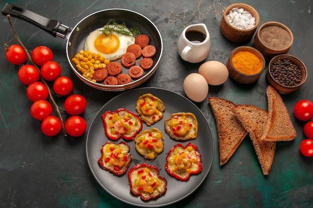 Bovenaanzicht gekookte paprika met roerei, kruiden en worstjes op het donkergroene oppervlak