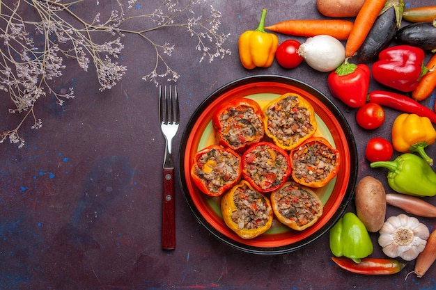Bovenaanzicht gekookte paprika met verschillende kruiden op donkergrijs oppervlak voedsel dolma plantaardige maaltijd rundvlees