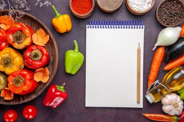 Bovenaanzicht gekookte paprika met verse groenten en kruiden op grijze oppervlakte maaltijd dolma plantaardige rundvlees