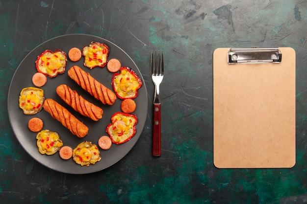 Bovenaanzicht gekookte paprika met worst en blocnote op donkergroen oppervlak