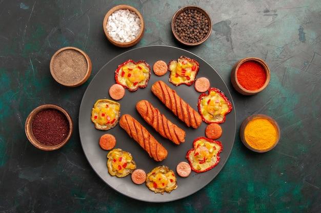 Bovenaanzicht gekookte paprika met worst en kruiden op het donkergroene oppervlak
