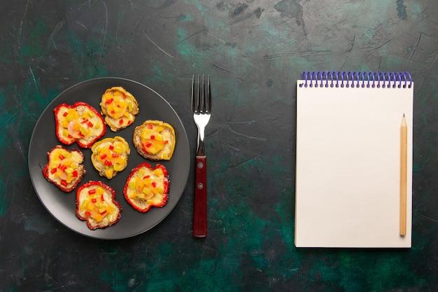 Bovenaanzicht gekookte paprika voor lunch in grijze plaat met blocnote op donkere ondergrond