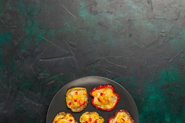 Bovenaanzicht gekookte paprika voor lunch in plaat op donkergroen oppervlak