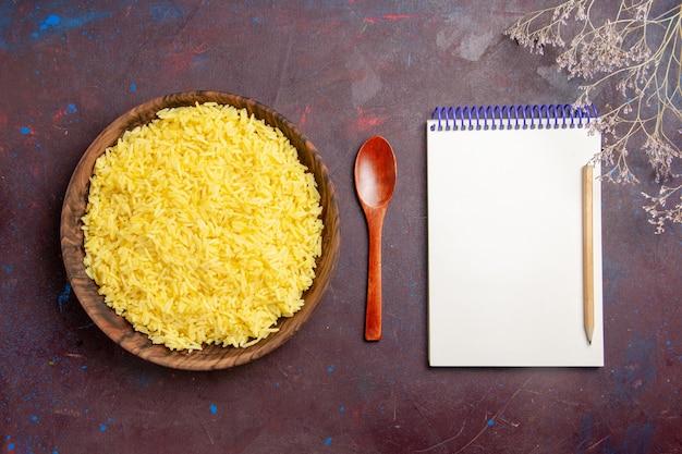 Bovenaanzicht gekookte rijst heerlijke maaltijd in bruine plaat op donker bureau