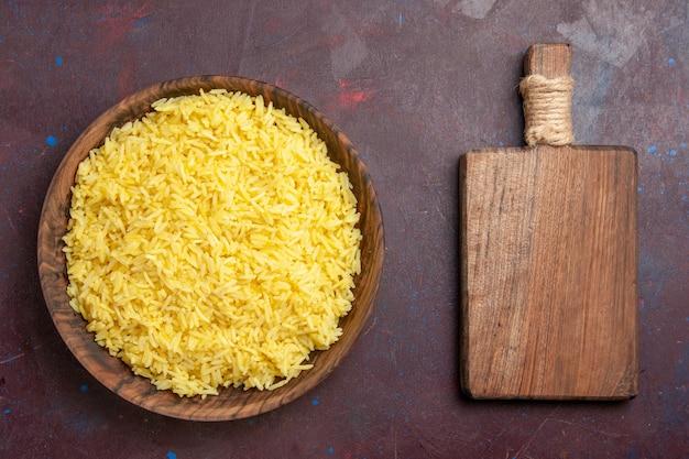 Bovenaanzicht gekookte rijst heerlijke maaltijd in bruine plaat op donkere ruimte