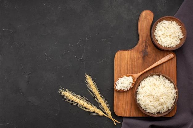 Bovenaanzicht gekookte rijst in borden op donkere ruimte