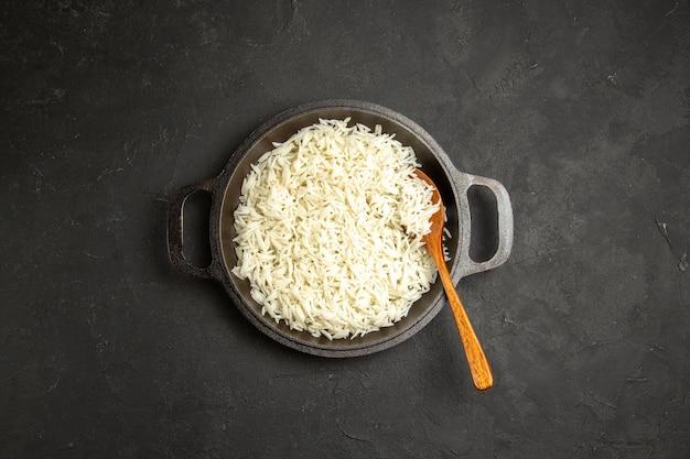 Bovenaanzicht gekookte rijst in pan op het donkere oppervlak diner maaltijd eten rijst oostelijk