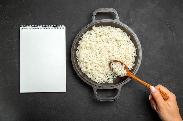 Bovenaanzicht gekookte rijst in pan op het donkere oppervlak maaltijd eten rijst oosters diner