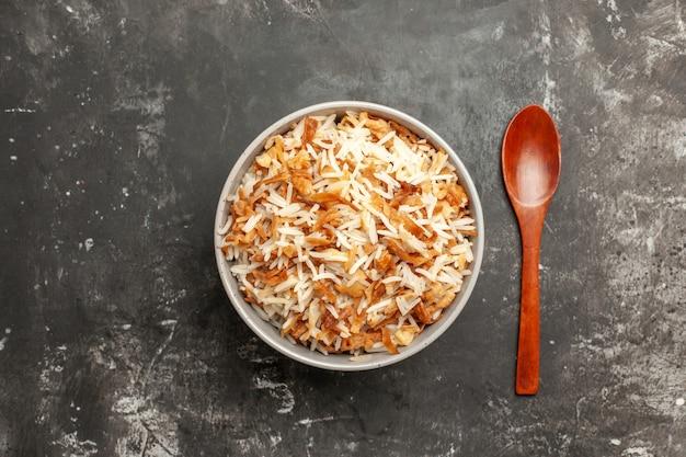 Bovenaanzicht gekookte rijst in plaat op donker oppervlak donker gerecht oost-maaltijdvoedsel
