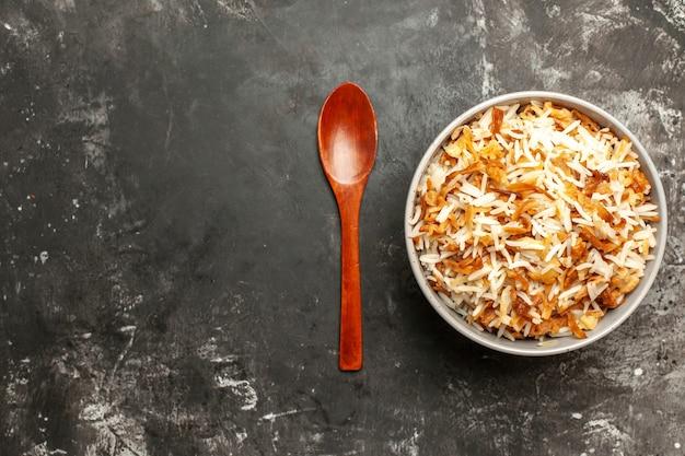 Bovenaanzicht gekookte rijst in plaat op donkere vloer donkere schotel oost-maaltijd eten