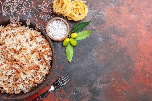 Bovenaanzicht gekookte rijst met deegplakken op de donkere foto van het de schotelvoedsel van de oppervlakte donkere maaltijd