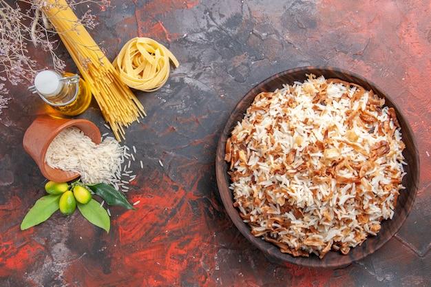 Bovenaanzicht gekookte rijst met deegplakken op de donkere schotel van de de fotomaaltijd van het oppervlaktevoedsel