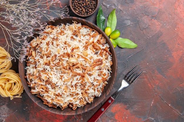 Bovenaanzicht gekookte rijst met deegplakken op donkere de schotel van de de schotelvoedsel donkere fotomaaltijd