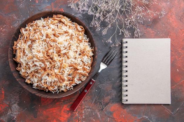 Bovenaanzicht gekookte rijst met deegplakken op donkere het voedsel van de de schotelmaaltijd van de oppervlaktefoto donker