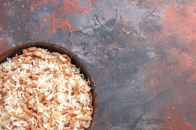 Bovenaanzicht gekookte rijst met deegplakken op donkere vloerschotel maaltijd donkere voedseldeegwaren