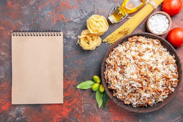 Bovenaanzicht gekookte rijst met rauwe pasta en tomaten op donkere ondergrond schotel donkere maaltijd voedsel foto