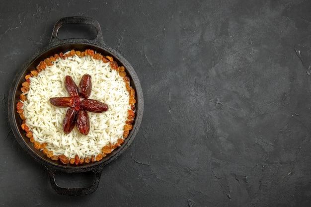 Bovenaanzicht gekookte rijst met rozijnen in pan op donkere bureaumaaltijd eten rijst oosters diner